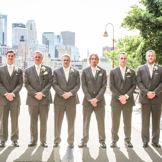 The couple's six groomsmen wore Vera Wang charcoal gray tuxedos with black dress shoes. Simple white roses and accents of hops made up their boutonnieres.