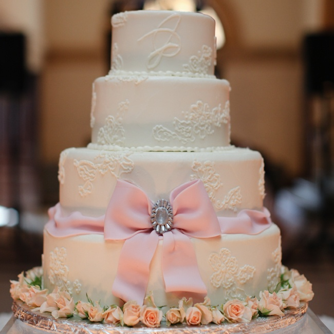 The four-tier white cake had a pink fondant bow and was accented with small blush roses around the base.