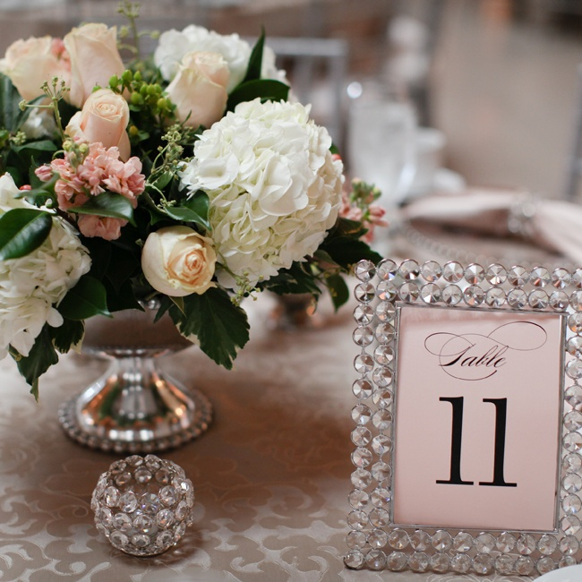 Low silver vases held bunches of blush and ivory roses, hydrangea and greenery. A rhinestone frame held the table number.