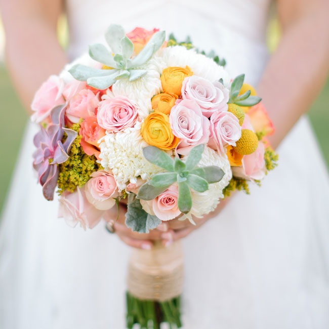 The bridal bouquet mixed pale green succulents with soft pink roses, yellow ranunculuses and white dahlias.
