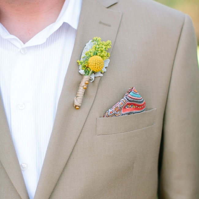 The groom accessorized his tan suit with a festive paisley pocket square and a yellow billy ball boutonniere wrapped in twine.
