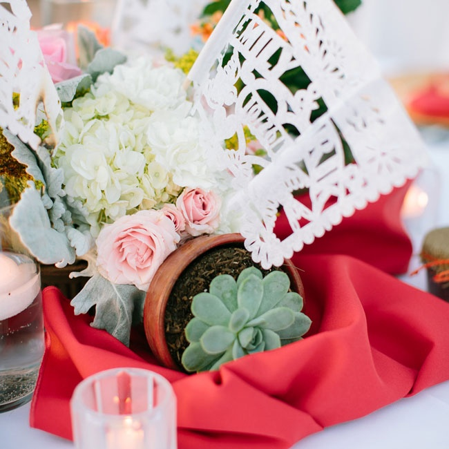 Centerpieces were made of hydrangeas, soft pink roses, succulents and laser cut paper flags with the couple's name.