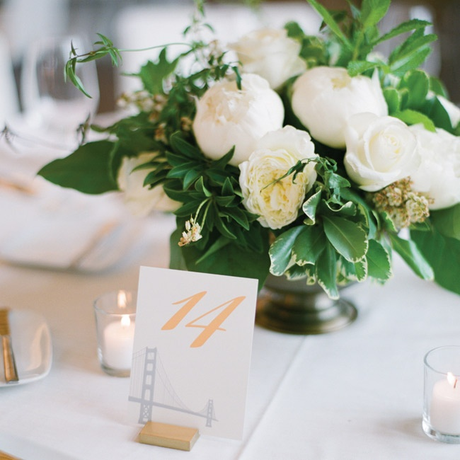The round tables were covered in white tablecloths and topped with either bronze-colored lanterns or white floral arrangements with candles. The couple incorporated the Golden Gate Bridge on their table number cards since they both lived in San Francisco.