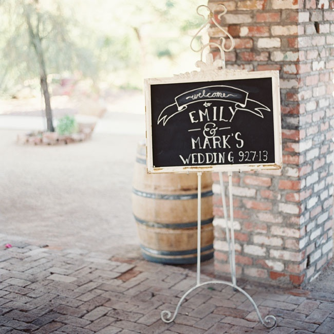 "A sign that read, ""Welcome to Emily & Mark's Wedding"" with the date greeted guests at the reception venue."