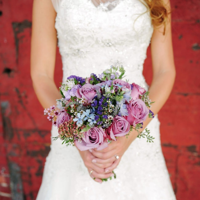 The bride carried this bouquet of various shades of purple roses and wax flowers down the aisle.