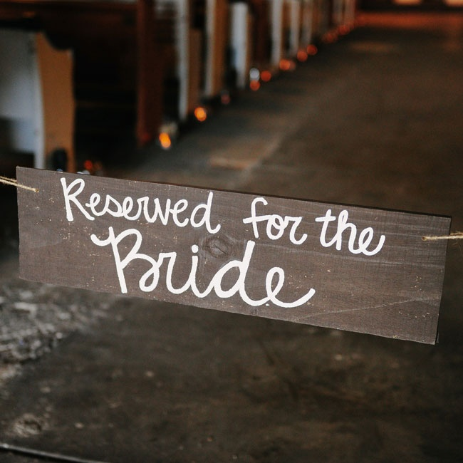 "The ceremony aisle was blocked by a wooden sign hand-painted to say, ""Reserved for the bride."""