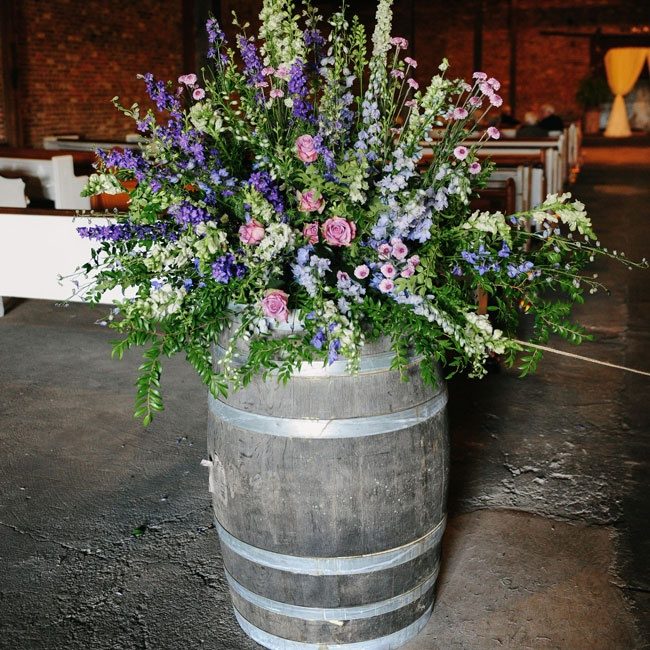 Various stock flowers in pink, purple, blue and white topped rustic barrels as an entrance point for the ceremony.