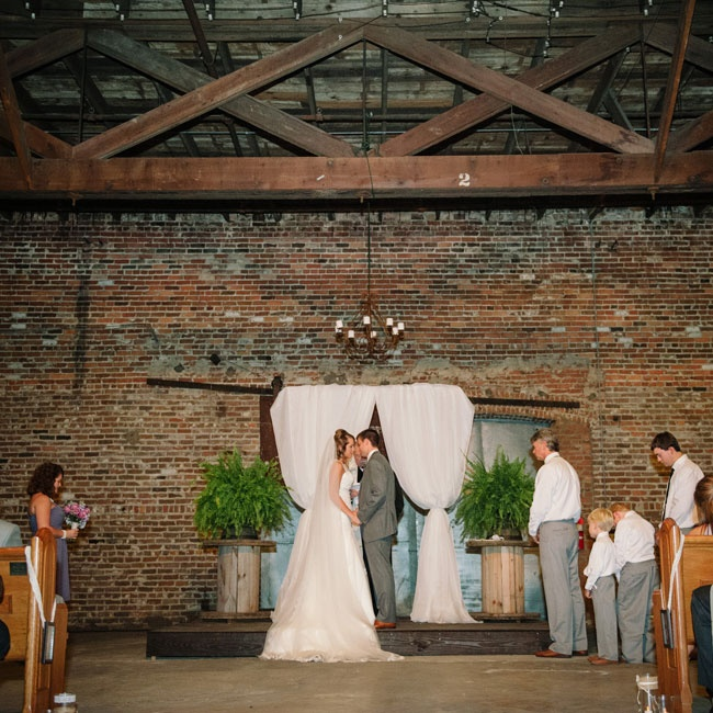 The couple got married with a backdrop of exposed brick and wooden beams.
