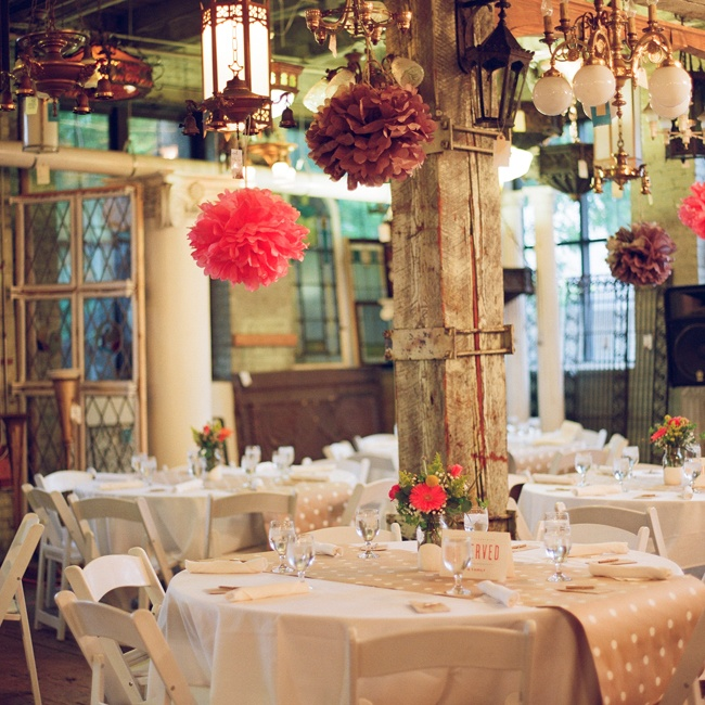 The couple created gray and coral paper poms that hung from the ceiling of Architectural Antiques. The guest tables were topped with more DIY creations like polka-dot Kraft paper runners and Mason jars filled with flowers.