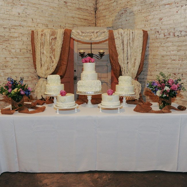Five separate cakes were displayed beneath a burlap and lace arch.