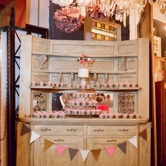 The cake and cupcakes were displayed on a rustic piece of salvaged furniture.