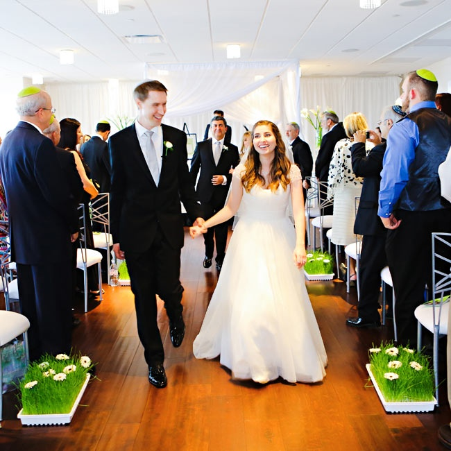 The ceremony aisles were lined with flowers and grass in white square pots.