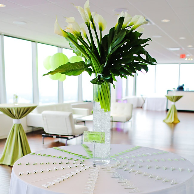 Guests' escort cards were displayed on a round table beneath a large calla lily centerpiece.