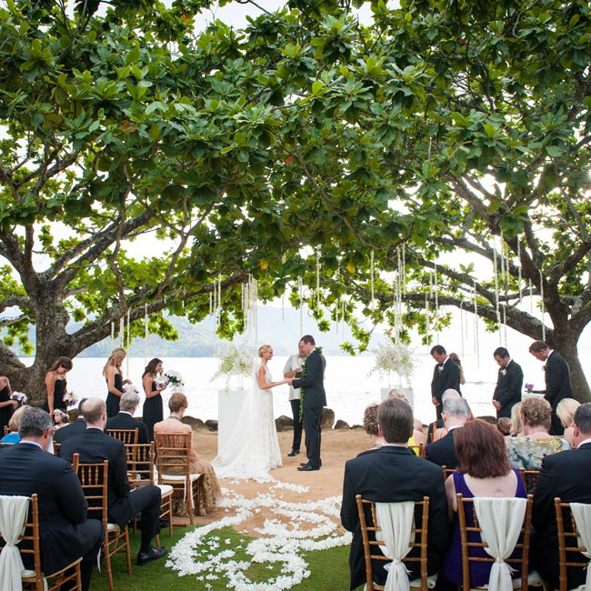 The ceremony took place outdoors beneath a canopy of trees and hanging decorations.