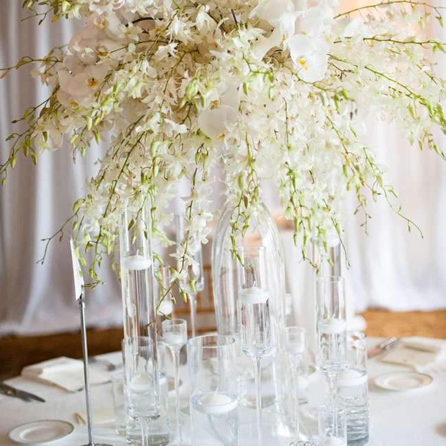 Floating candles in an array of clear vases encircled tall orchid centerpieces at the reception.