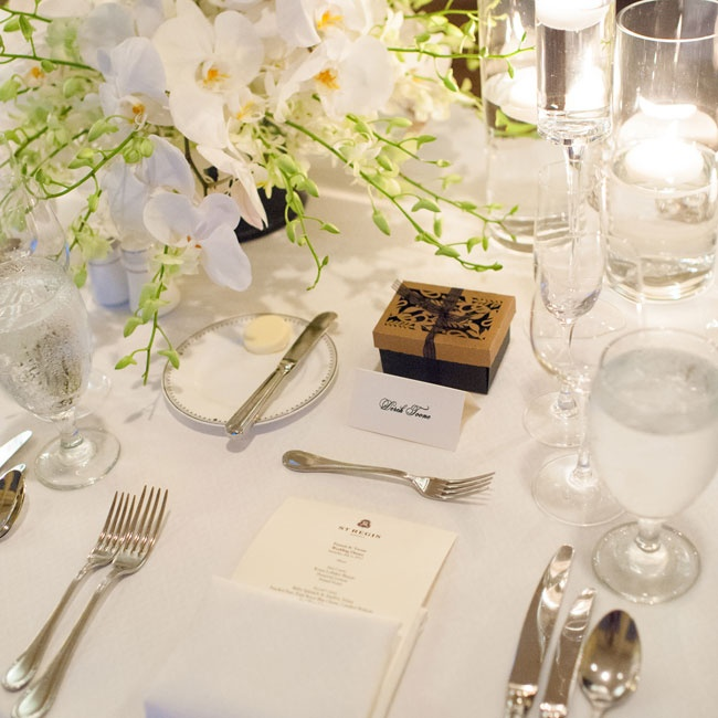 The place settings were mostly white with the exception of the small black and gold favor boxes.