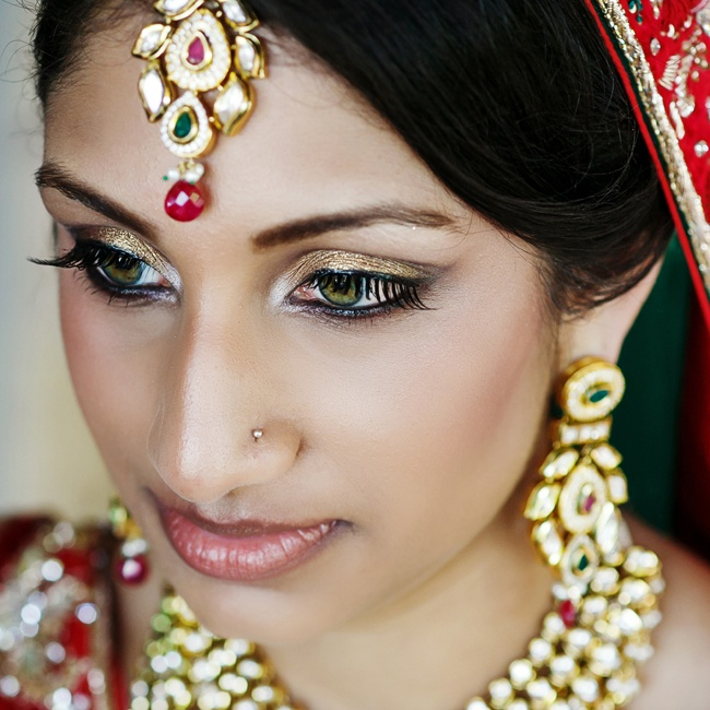 The bride's beauty and accessory look was traditional with a matching set of gold jewelery with green and red accents.