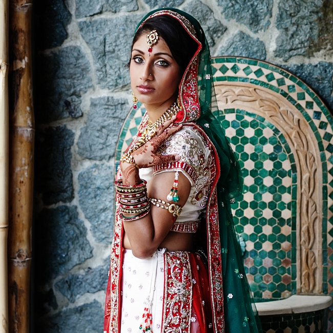 The bride wore traditional Indian wedding garb in white, red, green and gold.