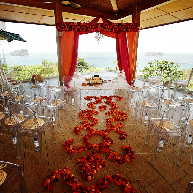 The ceremony location overlooked the Punta De Vista ocean views and employed modern clear chairs mixed with lush loose petal floor designs and other red decor.