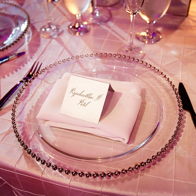 Guests dining places were set with clear chargers accented with gold beads and a folded white linen napkin beneath a formal place card.