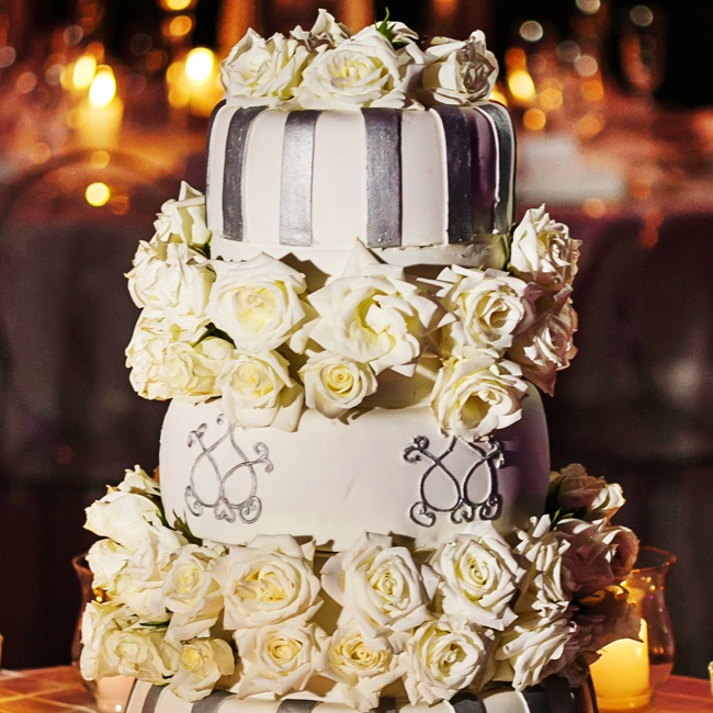 The wedding cake was a white and silver confection in three tiers with layers of white roses between layers.