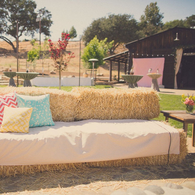 The expansive backyard of Laura's family home was transformed into a country style lounge for cocktail hour. Guests sipped beverages while lounging on haystack lounge furniture covered with bright pillows and neutral linens.