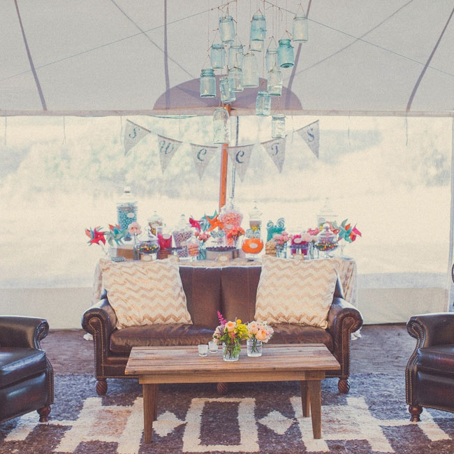 Guests could step out of the hot summer sun and relax under the shade of the reception tent. Dark leather furniture, southwestern style rugs and wooden accents came together for a rustic chic lounge look.