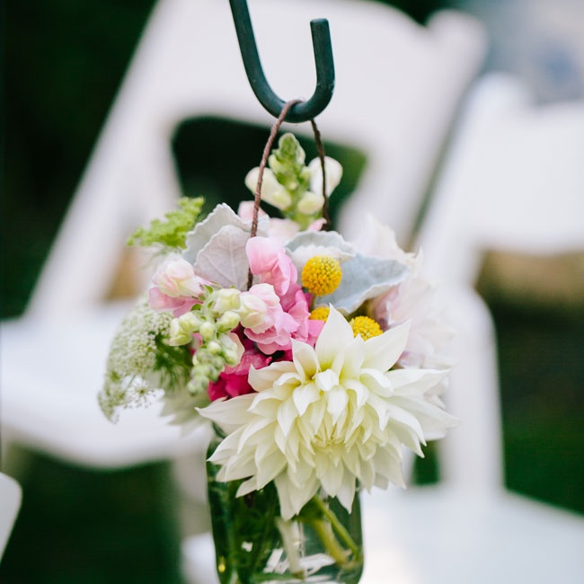 Textured bunches of bright blooms arranged in mason jars lined the aisles. Pink stock and billy balls added a fresh pop of color to the muted hues of the dahlias and lamb's ear.