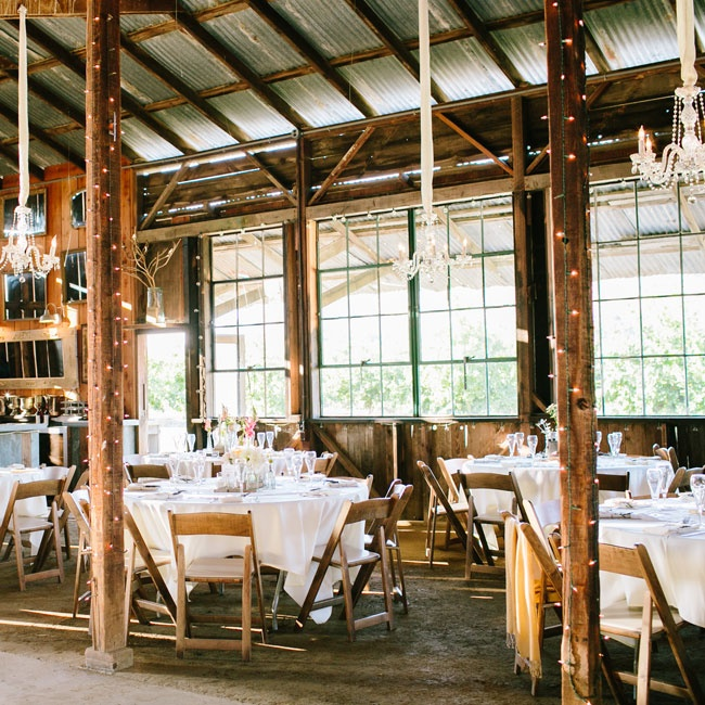 The reception was held in the Dana-Powers House's rustic barn. Elaborate chandeliers, bistro lighting, a gallery wall of gilded mirrors and crisp white linens brought an elegance to the space.