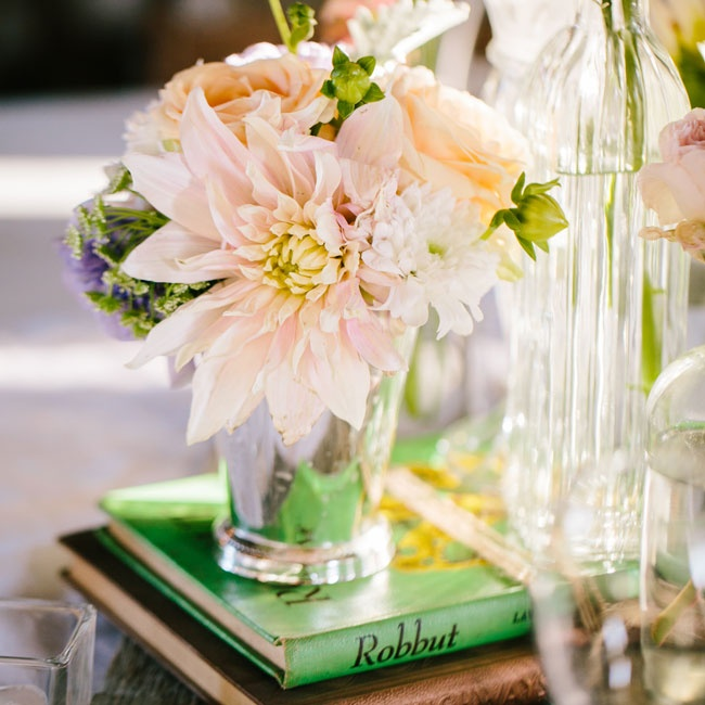 The centerpieces were composed of pastel blooms like dahlias and roses in mix of simple glass vases. Vintage books and distressed wooden planks gave the centerpieces a shabby-chic feel.