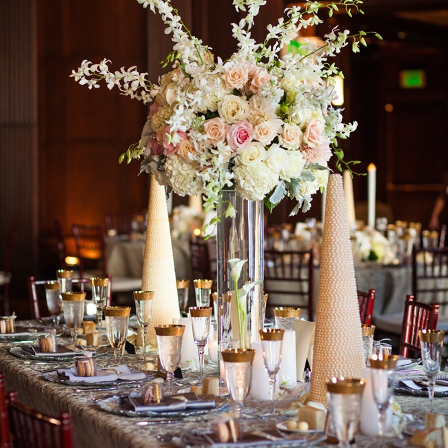 Lavish high floral arrangements with pastel blooms and pearl cone centerpieces decorated the luxurious reception tables, adding warmth to the cool silver palette of the linens and place settings.