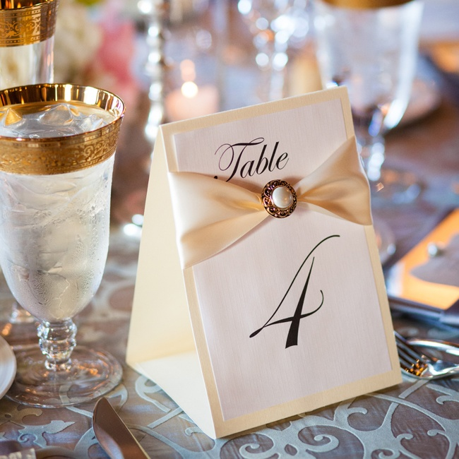 Simple tented table numbers were given an elegant update with satin bows fastened with pearl buttons.