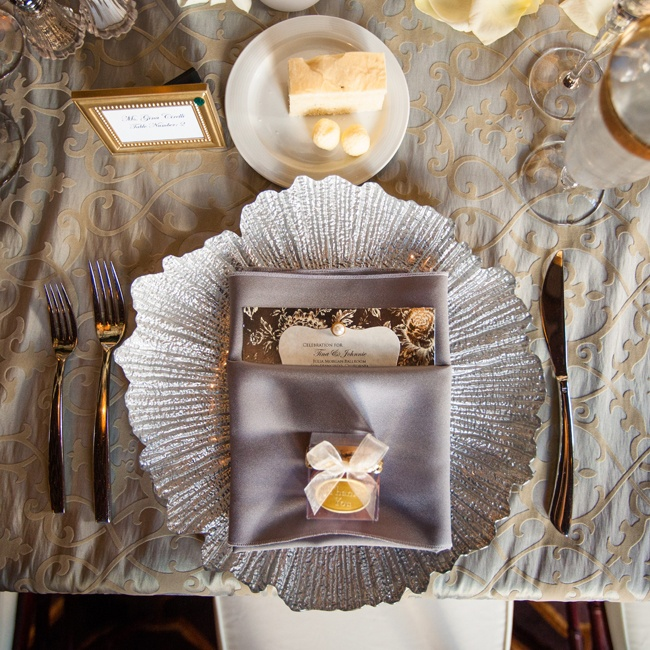 The couple gave their reception tables an instant style upgrade with textured, silvery china, an elegant patterned table cloth and linens in complementary metallic hues. Gilded frame escort cards and gold-accented wine glasses picked up on the champagne colored thread in the table cloth.