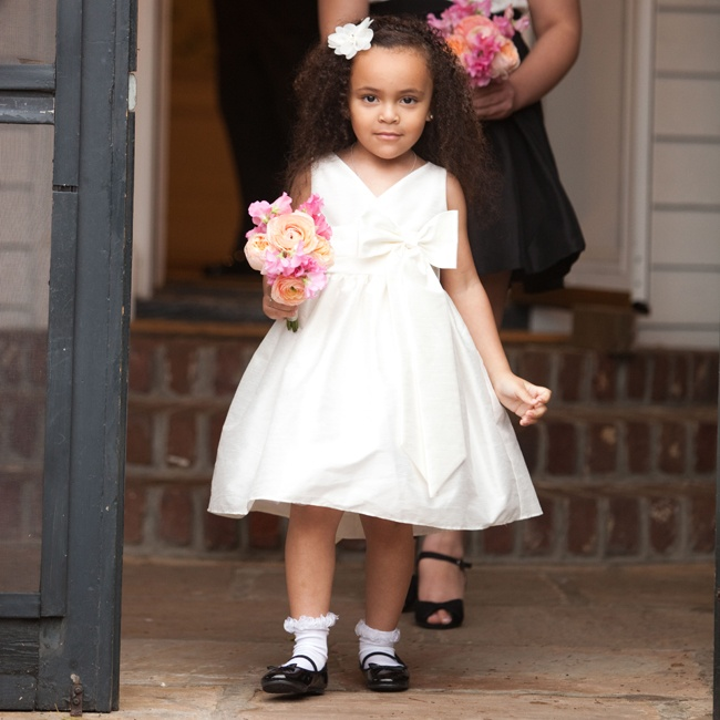 The flower girl wore and adorable knee-length dress with a full skirt and bow embellishment. A flower hair clip and a pair of patent Mary Jane shoes completed the look.