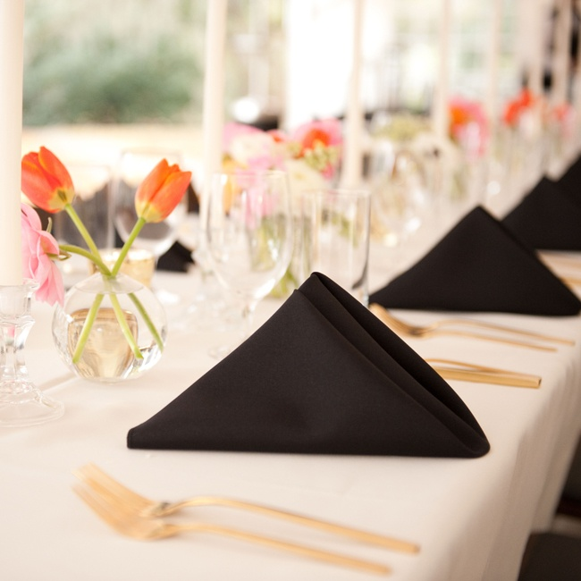 Black and white linens, golden cutlery and simple bud vases with colorful tulips gave the reception tables a modern edge.