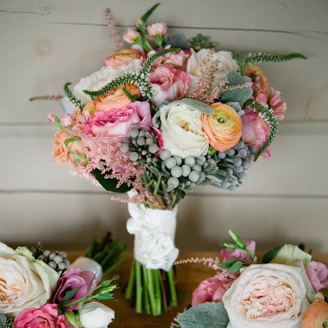 Paula's bouquet mixed bright blooms like roses and ranunculuses with cool blueish gray accents like berzelias and lamb's ear.