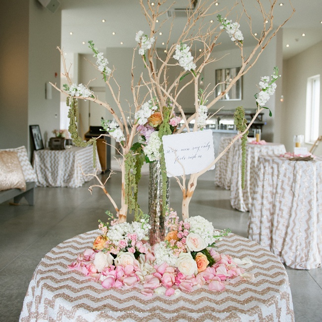 Shimmery rose gold and white sequined table cloths in a chevron print covered the cocktail tables. The main table was decorated with a whimsical arrangement of tree branches, hanging moss and a bright mix of roses, hydrangeas and stock flowers.