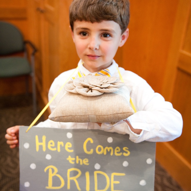 "The ringbearer came down the aisle with a ""Here Comes the Bride"" sign and a burlap ring pillow with a floral embellishment."