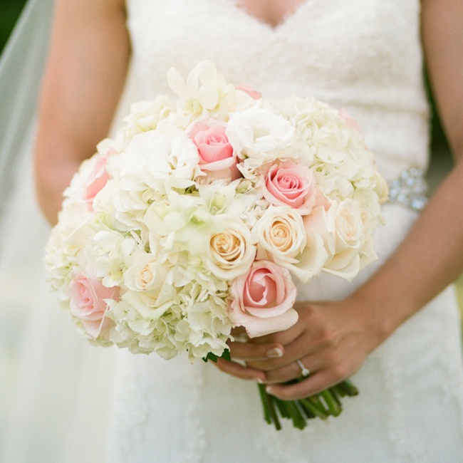 The bride carried a classic bouquet of roses and hydrangeas down the aisle.