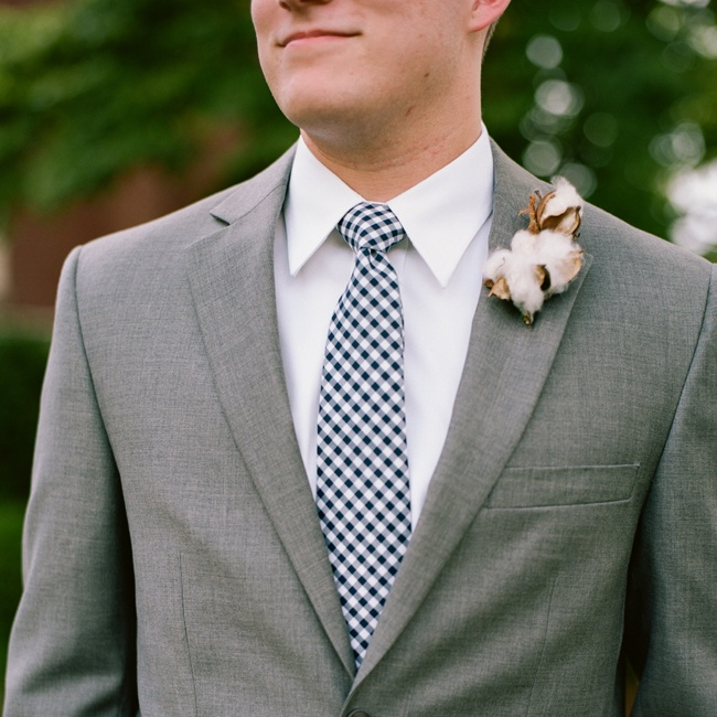 The groom wore a boutonniere of freshly picked cotton on his heathered gray suit. He accessorized with a navy gingham tie.