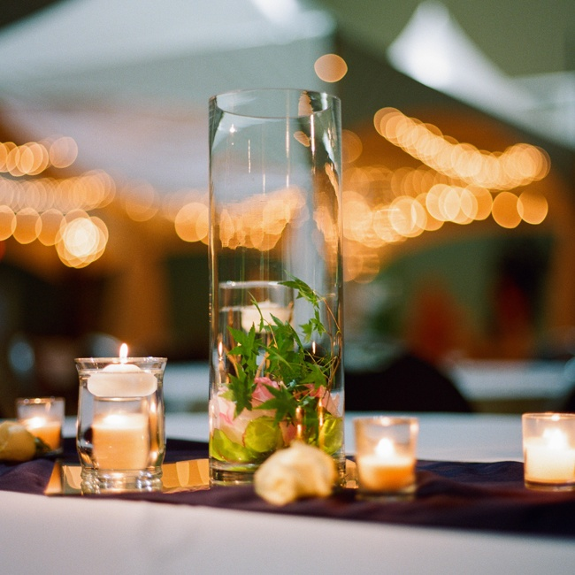 Lit candles in different arrangements made for intimate centerpieces at the reception.