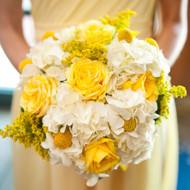 The bridesmaids walked down the aisle with bright bouquets of roses, hydrangeas, and billy balls.