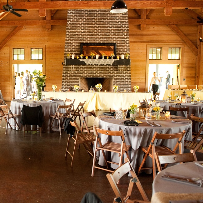 The couple and their guests headed to the Pavilion at Pepper Plantation. The modern barn-style venue had exposed wooden beams, cathedral ceilings and a towering brick fireplace that gave the space a rustic feel. The couple decorated with simple, rustic decor in a modern yellow and gray color palette to complement the setting.
