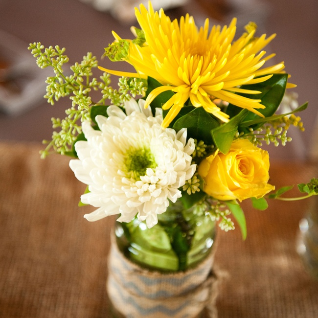 Bright yellow mums and roses accented with eucalyptus seeds arranged in chevron burlap-wrapped mason jars made for cheerful centerpieces with a rustic touch.