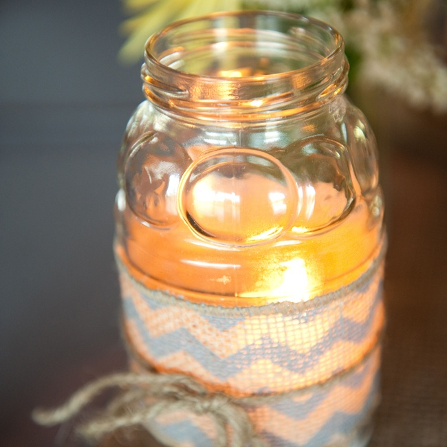 Mason jar candles wrapped in chevron burlap matched the centerpieces and gave off a warm ambient glow.