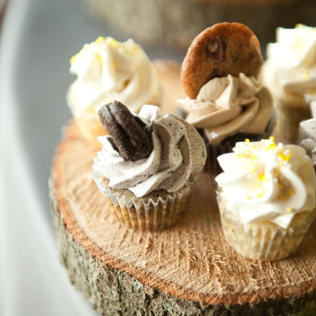 An assortment of cupcakes were displayed on tree trunk slices for a rustic, woodland feel.