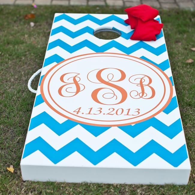 During cocktail hour, guests were invited to play lawn games like cornhole. The board was decorated in a modern blue chevron print and red monogram that complemented the day's color scheme.