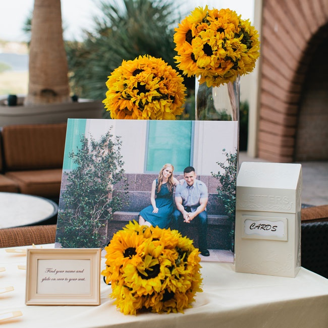 Bright summer sunflowers were arranged on top of simple hurricane vases creating a cheerful, yet modern look for the reception entryway.
