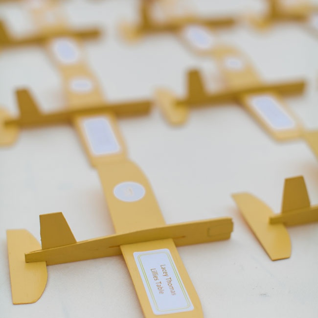 The couple made these fun airplane escort cards using balsa wood, yellow paint and address labels.