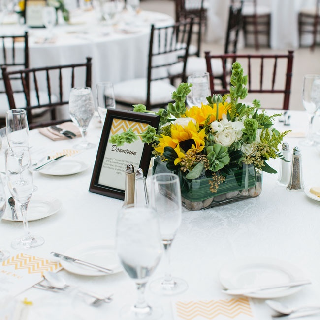 Sunflowers, ranunculuses and lush greenery arranged in contemporary low glass vases filled with pebbles brought a fresh pop of color to the elegant white table linens.